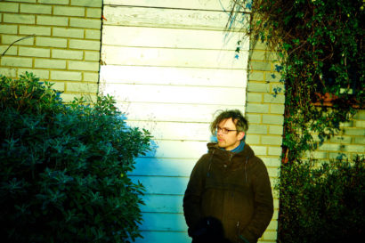 Benbo, standing in front of a wood-panelled exterior wall, looking at shrubs to his right